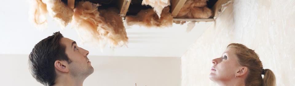 stel kijkt naar kapot plafond door lekkage